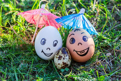 Funny eggs imitating happy mixed parents with versicolored baby Royalty Free Stock Photos