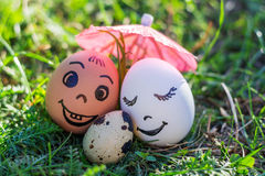 Funny eggs imitating smiling mixed couple with versicolored baby Royalty Free Stock Photography