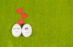 Funny eggs in love on a green grass. Royalty Free Stock Image