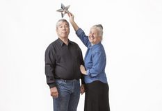 Funny Elderly Couple. Elderly couple with wife holding a silver star atop husbands head isolated against a white background Royalty Free Stock Photo