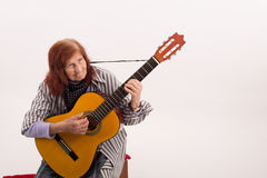 Funny elderly lady playing acoustic guitar Royalty Free Stock Photography