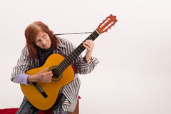Funny elderly lady playing acoustic guitar Royalty Free Stock Photos