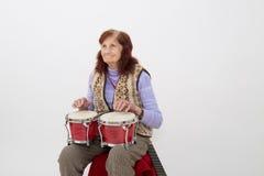 Funny elderly lady playing bongo Royalty Free Stock Photos
