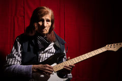 Funny elderly lady playing electric guitar Stock Image
