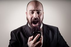Funny elegant bearded man screaming on the phone. On vignetting background Stock Image