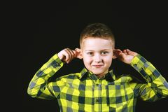 Funny emotional boy. Child holding himself by the ears Stock Photos