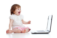 Funny emotional child girl using a laptop Royalty Free Stock Photo