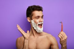 Funny emotional guy talking with a shaver royalty free stock photography