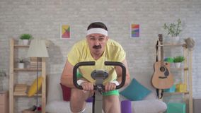 Funny energetic athlete from the 80`s with a mustache engaged at home on a exercise bike slow mo