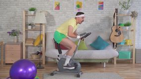 Funny energetic man from the 80s with a mustache engaged at home on a exercise bike slow mo. Funny energetic man athlete from the 80s with a mustache engaged at stock footage
