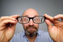 Funny european man looking through glasses. Have problems with eyesight. His eyes are looking very small royalty free stock photos