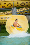 Funny excited child enjoying summer vacation in water park ridin Stock Images