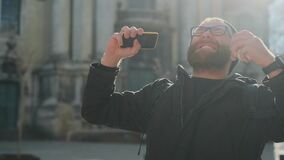 Funny excited man in glasses with paper coffee cup looking at phone screen while standing at street. Bearded guy using