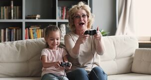 Funny excited two generations family gamers play video game at home