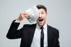 Funny excited young businessman covered one eye with money Royalty Free Stock Photography