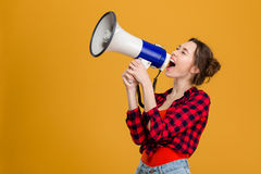 Funny excited young woman shouting in megaphone Royalty Free Stock Images