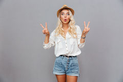 Funny excited young woman showing peace sign. Over gray background stock photo