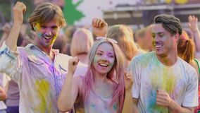 Funny excited youngsters actively dancing at Color festival, extra-slow motion