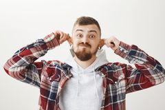 Funny expresive guy stretching ears over gray wall. Portrait of attractive carefree young european male in stylish. Outfit pulling ears up, wearing flesh Stock Image
