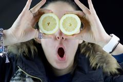 Funny expression for girl holding two half lemons. Covering her eyes, healthy lifestyle Stock Photos