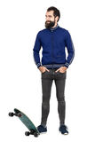 Funny expression of happy hipster in tracksuit standing on skateboard Royalty Free Stock Image