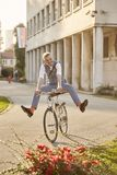 Funny expression legs spread, one young man, 20-29 years old, wearing hipster suit, smart casual, riding cycling old city bike stock photo