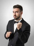 Funny expression of new groom holding clenched fist gesture with wedding ring. Portrait over gray studio background Stock Photography