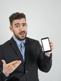 Funny expression of young businessman showing broken cellphone screen Royalty Free Stock Photo