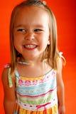 Funny face. Cute little girl wearing sundress set against orange backdrop Royalty Free Stock Image