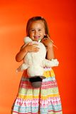 Funny face. Cute little girl wearing sundress set against orange backdrop holding her favorite stuffed animal Stock Photo
