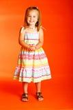 Funny face. Cute little girl wearing sundress set against orange backdrop Royalty Free Stock Photo