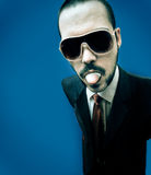 Funny face. Young caucasian guy in suit and funny pink sunglasses, sticking out his tong, chewing gum stock image