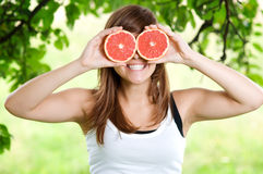 Funny face. Young woman having fun with fruits Stock Photos