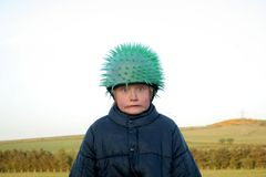 Funny Face. A child in the countryside making a face, wearing a funny hat Stock Photo