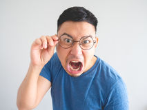 Funny face of angry Asian man. Stock Image