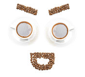 Funny face arranged from coffee beans and mugs Stock Images