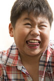 Funny face. An Asian boy close up portrait shot doing a funny face isolated on white background Stock Photos