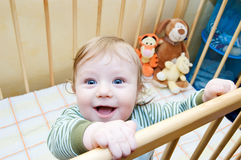 Funny face of baby boy. Playing in bed stock photo