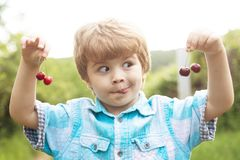 Funny face. Baby child with cherries in two hands. Fun math. Equations. Summer holidays. Happy time. Garden with fruit stock photography