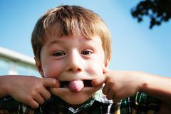 Funny Face Boy. Portrait of a young boy making a funny face by stretching his mouth with one finger of each hand.  Taken in an outdoor setting.  Horizontal Royalty Free Stock Image