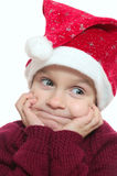 Funny face of child wearing red Santa�s hubcap. Royalty Free Stock Images