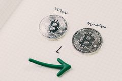Funny face crazy bitcoin lover, using 2 bitcoin coins as eyes dr. Awing nose on gridline notebook with smiling green price rising arrow mouth stock photography
