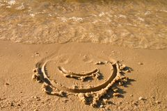 Funny face drawn on wet sand near sea Royalty Free Stock Photography