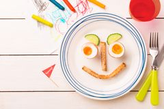 Funny face - kid`s breakfast - eggs, toasts and cucumber royalty free stock photos