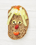 Funny face made of bread, butter, sausage, black pepper and toma Stock Images