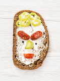 Funny face made of bread, butter, sausage, paprika, black pepper Stock Image