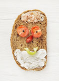 Funny face made of bread, butter, tuna, sausage, black pepper an Stock Photo