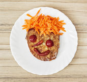 Funny face made of bread, carrot, chilli, tomatoes and ketchup - Stock Photo