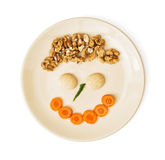 Funny face made of carrot, biscuits and walnuts on the plate, cr Royalty Free Stock Photo