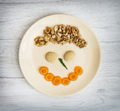 Funny face made of carrot, biscuits and walnuts on the plate, cr Royalty Free Stock Image
